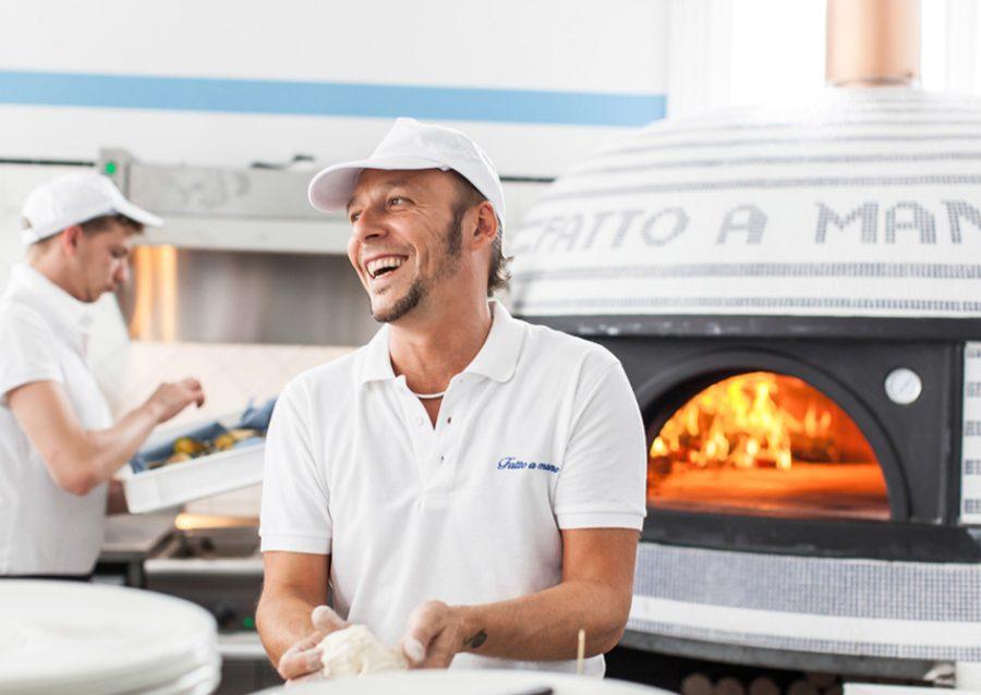 fatto a mano chef smiling near oven